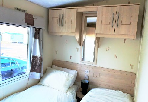 Twin bedroom with over head cupboards.