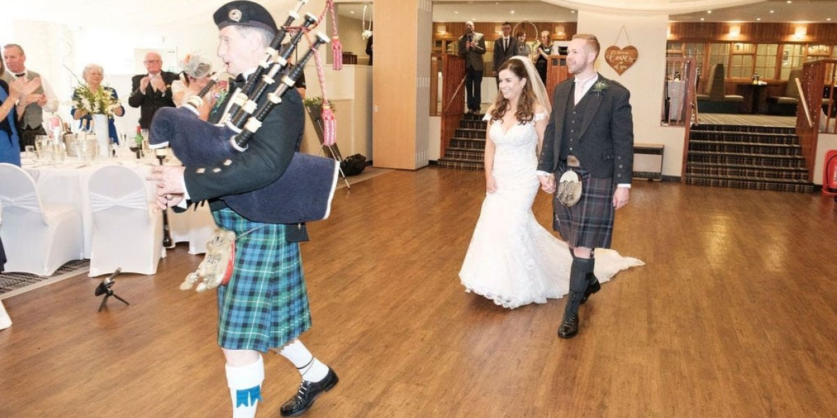 A couple being lead out by bagpipes at a Scottish Wedding