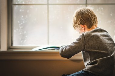 A young boy reading by a window